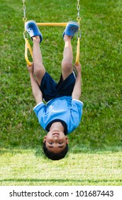 Child Hanging Upside Down on Monkey Bars in Playground