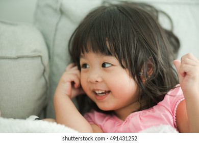child and happiness concept - smiling little asian girl on sofa at home