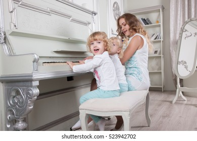 Child. Happy Children Playing the Piano with her mother.  Piano school for little girl.