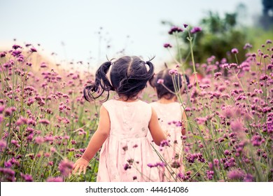 Child happy little girl  running and having fun in the purple flower field in vintage color tone