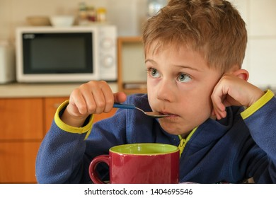 child has breakfast with a red cup and a spoon in his mouth against a blurred microwave background