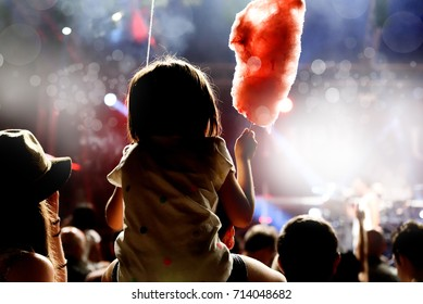 Child has fun on her parents' shoulders at an outdoor rock music concert when eating her candy floss