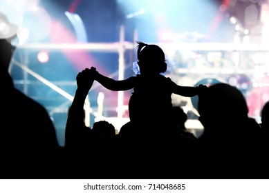 Child has fun on her parents' shoulders keeping hands with them at an outdoor rock music concert