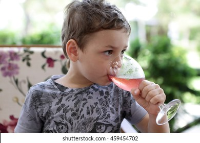 Child has juice in an outdoor cafe