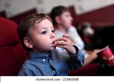 The child has popcorn in the cinema