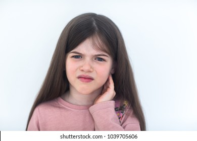 Child has a sore ear. Little girl suffering from otitis. Isolated on white background