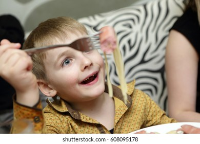 Child has spaghetti with sausage in a restaurant