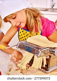 Child in hat making homemade pasta at kitchen.
