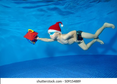 Child in hat Santa Claus swims underwater with a gift in hand on blue background. The view from under the water. Horizontal orientation