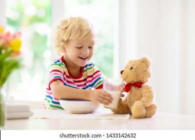 Child having breakfast. Kid feeding teddy bear toy, drinking milk and eating cereal with fruit. Little boy at white dining table in kitchen at window. Kids eat. Healthy nutrition for young kids.