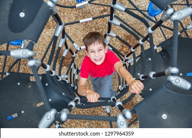 child having fun on outdoor playground. boy climbs up the Jungle Gym