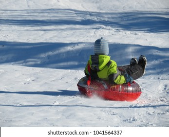 Child having fun on snow tube. Boy is riding a tubing. Winter entertainment