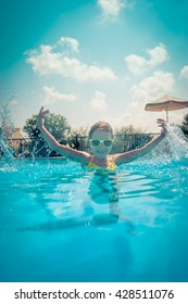 Child having fun in swimming pool. Kid playing outdoors. Summer vacation and healthy lifestyle concept