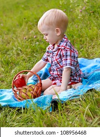 Child having picnic on the green meadow in summer day