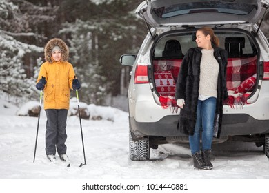 Child having sport activity in forest and mother standing in fur coat near back of car. Winter season