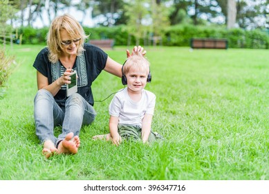 Child in headphones is listening music from mom`s phone