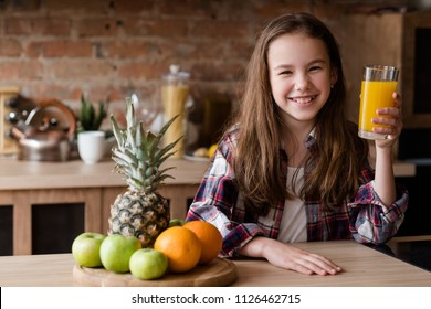 child healthy food and balanced nutrition. fresh orange juice and fruit breakfast. smiling little girl in the kitchen ready to have a wholesome morning meal