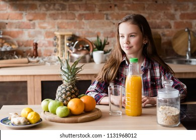 child healthy food and balanced nutrition. fresh fruit juice and oatmeal breakfast. little girl in the kitchen ready to have a wholesome morning meal