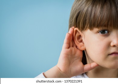Child with hearing problem on blue background. Hearing loss, symptoms and treatment concept. Close up, copy space.