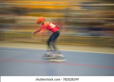 Child in a helmet in motion, riding on rollers - abstraction