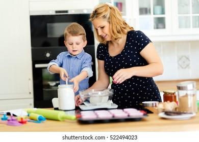 Child helping mother make cookies in modern kitchen