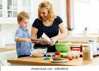 Child helping mother make cookies