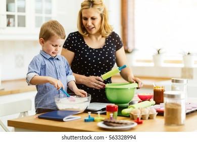 Child helping mother prepare muffins in kitchen