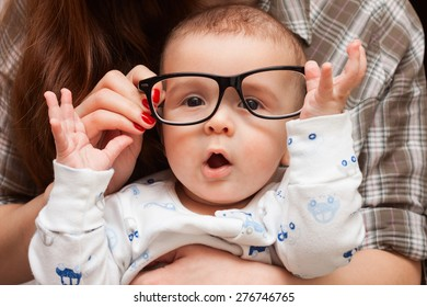 a child in her mother's glasses. funny baby in glasses
