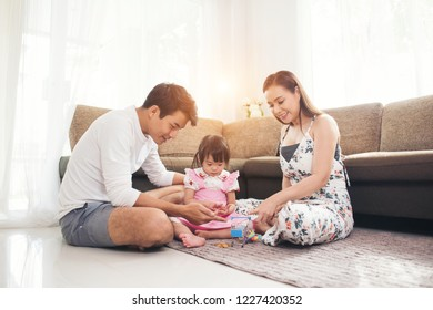 Child with her parent playing on floor in living room