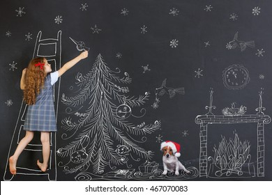 Child and her puppy decorates a Christmas tree drawing on blackboard. Christmas holiday concept.