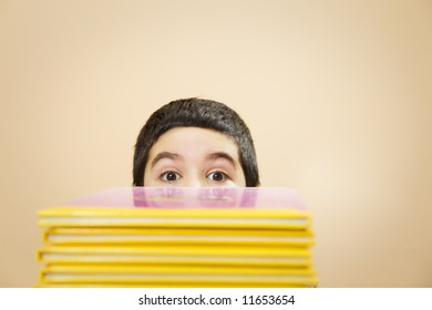 child hidden behind a pile of books of fairy tales