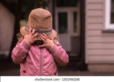 Child hiding her face under big adult summer straw hat