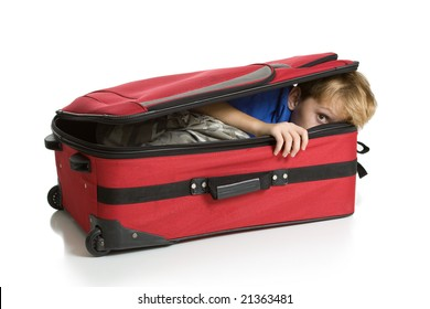 Child hiding inside a red suitcase. Isolated on a white background.