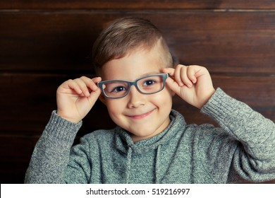 Child hipster smiling on wooden background. A kid likes the glasses.