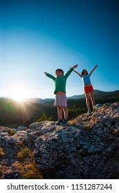 A child with his mother on top of a mountain at sunset. The boy enjoys climbing to the top. The woman and her son raised their hands up. Traveling with children.