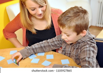 A child and his mother play a social game together at home