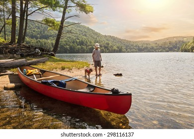 a child and his pet dog playing on the shore of a lake after canoeing during a beautiful, summer sunset