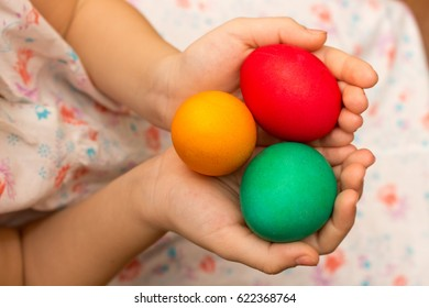 Child hold colorful painted Easter eggs in hands , top view.