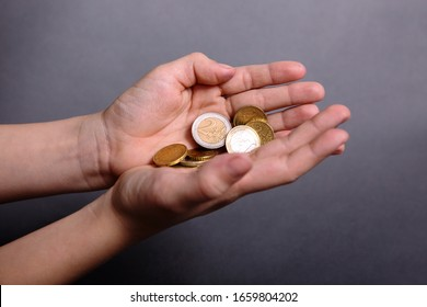 child hold in his little hands money euro on grey background