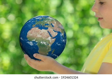 Child holding 3D planet in hands against green blurred background. Earth day spring holiday concept. Elements of this image furnished by NASA