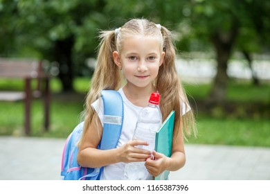 The child is holding a book and a bottle of water. The concept of school, study, education, friendship, childhood