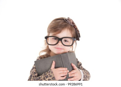 Child holding a book, wearing large glasses