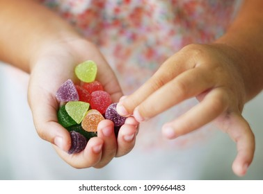 Child holding candy , jelly in hand