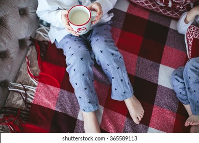 child holding a cup of milk sitting on the couch