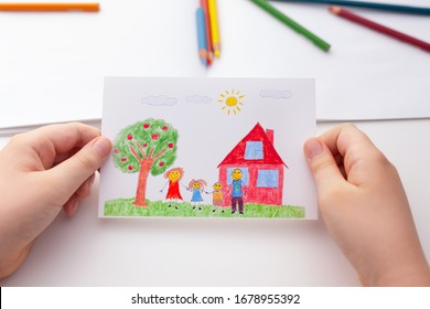 Child holding a drawing with a happy family and an apple tree and a house. Close up.