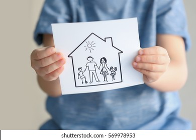 Child holding drawing of house with family, closeup. Adoption concept