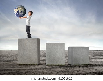 Child holding the earth and standing on the highest of three cubes on a field