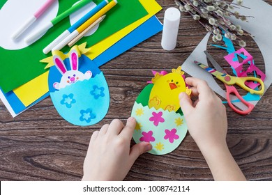 A child is holding an Easter egg gift with a chicken and Easter bunny toy. Handmade. Project of children's creativity, handicrafts, crafts for kids.