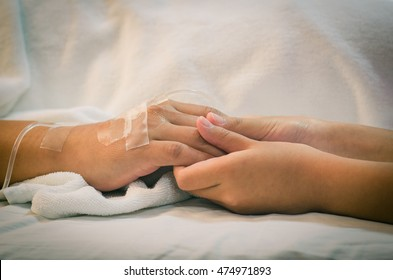 Child holding father's hand who fever patients have IV tube.