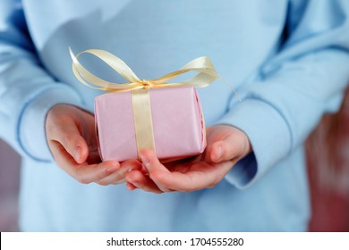 Child Holding a Gift Box On a Blue Background